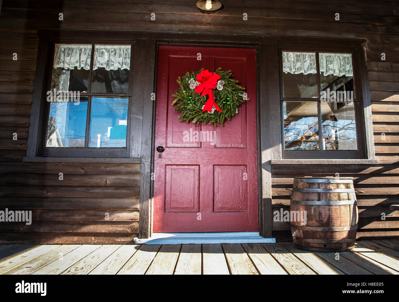 Christmas wreath on a red cabin front door, rain barrel, New Jersey ...