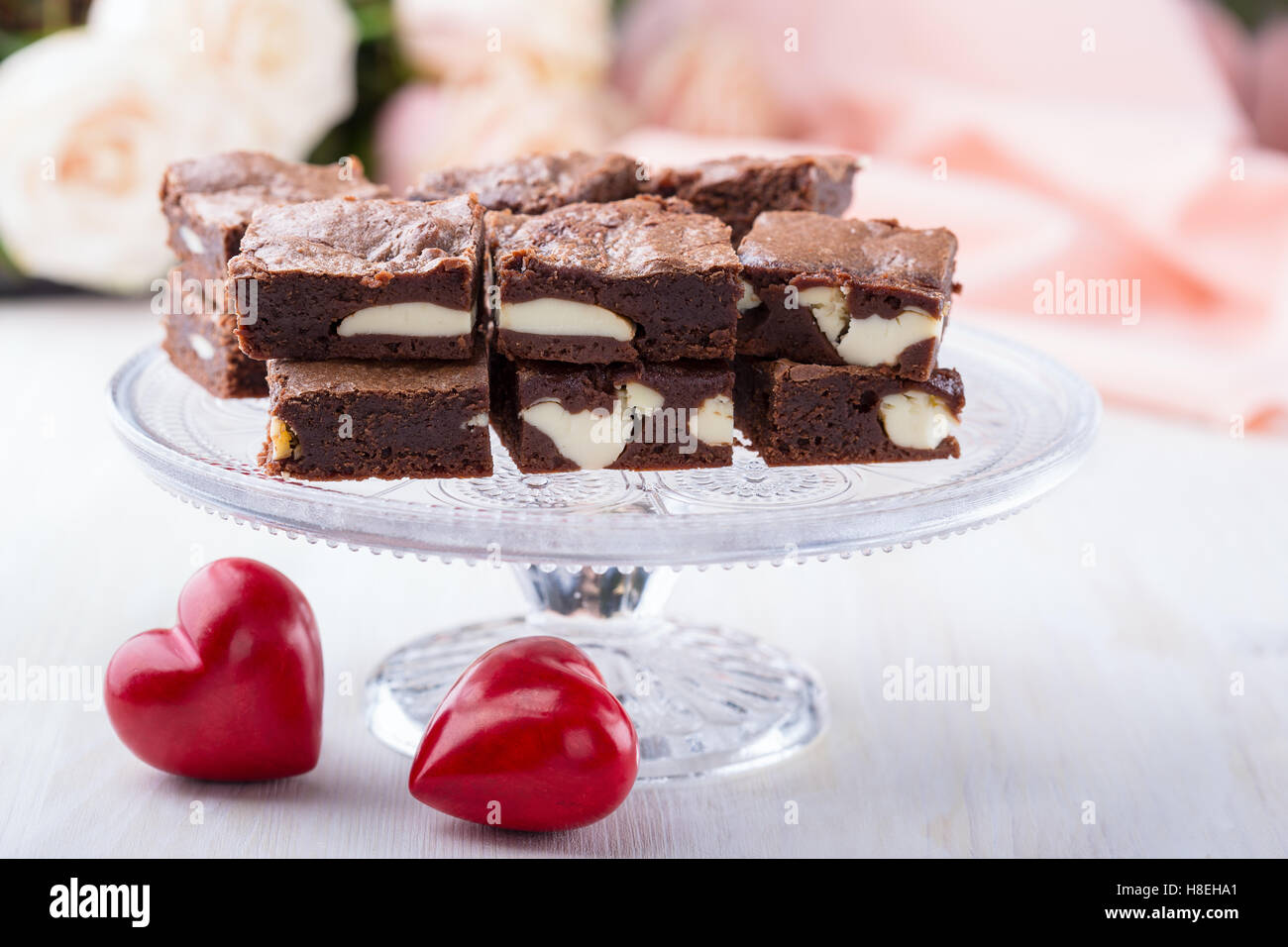 Valentines day cheesecake brownies on cake stand on pink roses background - Stock Image