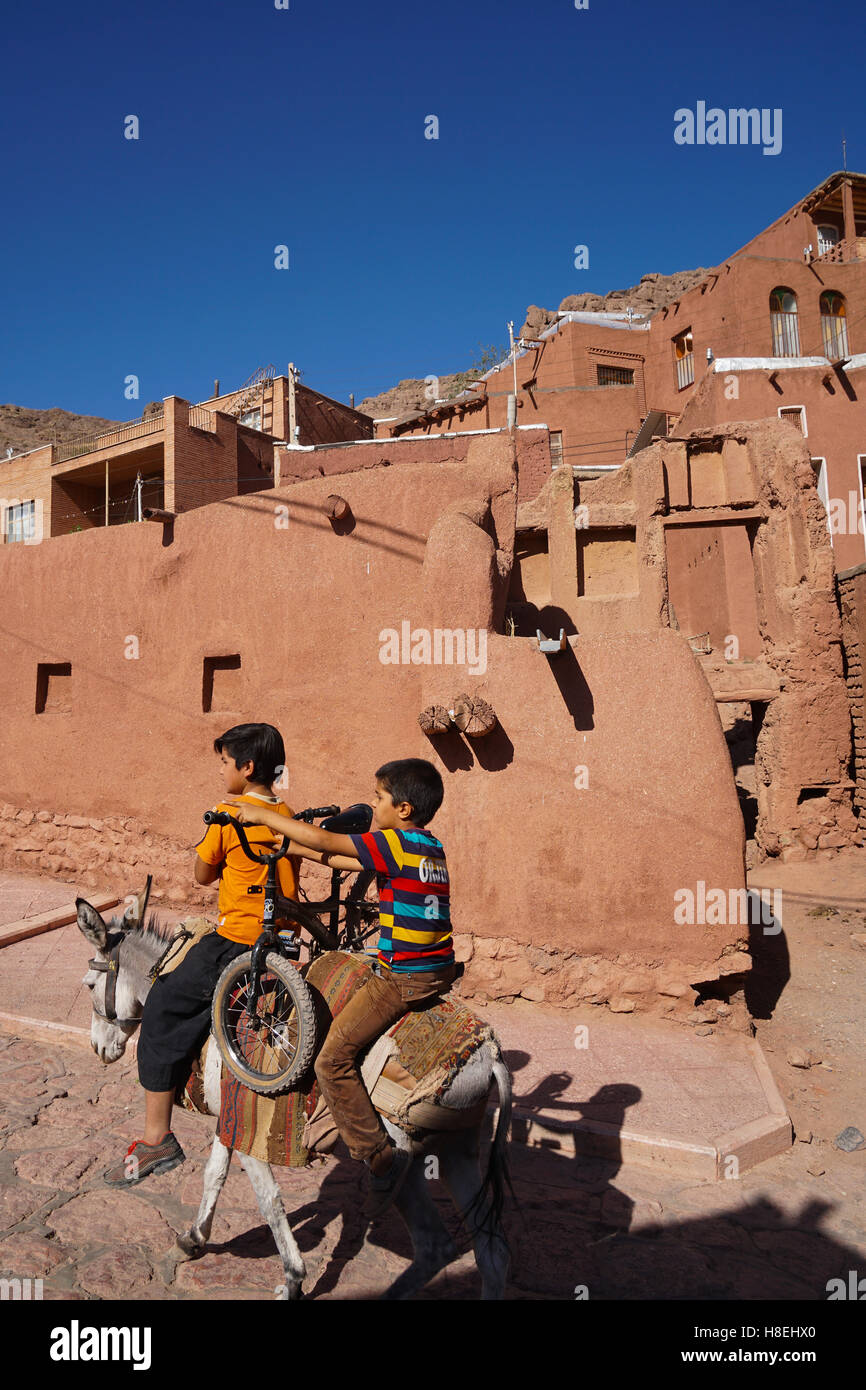 Boy with donkey gives bicyclist a lift in 1500 year old traditional village of red mud brick houses, Abyaneh, Iran, - Stock Image