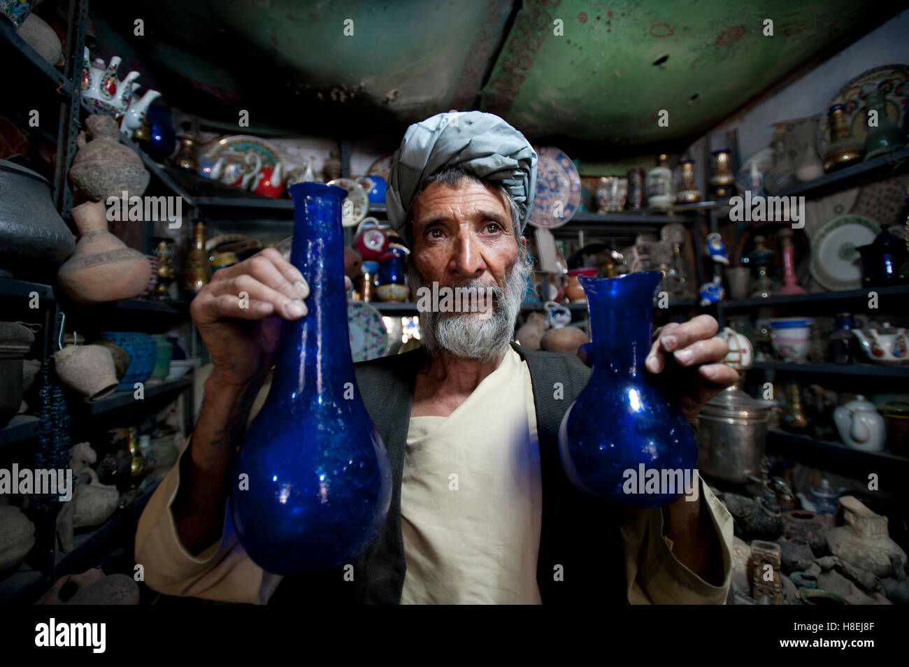 A glass blower holds up blue glass gourd-shaped vases in a trinket shop in Herat, Afghanistan, Asia - Stock Image