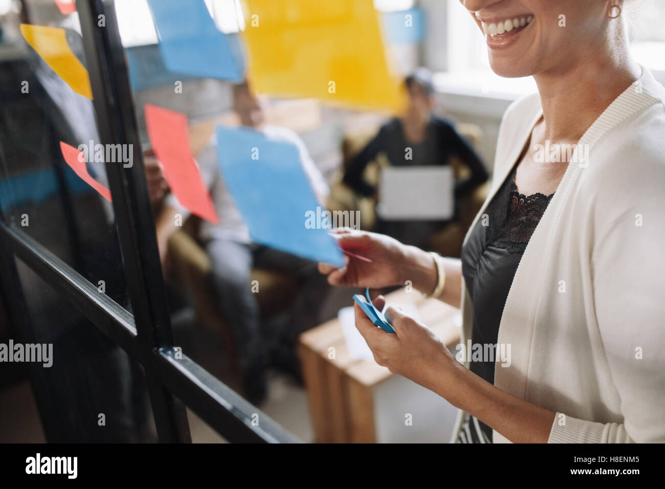 Smiling young woman brainstorming using adhesive notes on glass wall. Presenting ideas to colleagues during meeting. - Stock Image