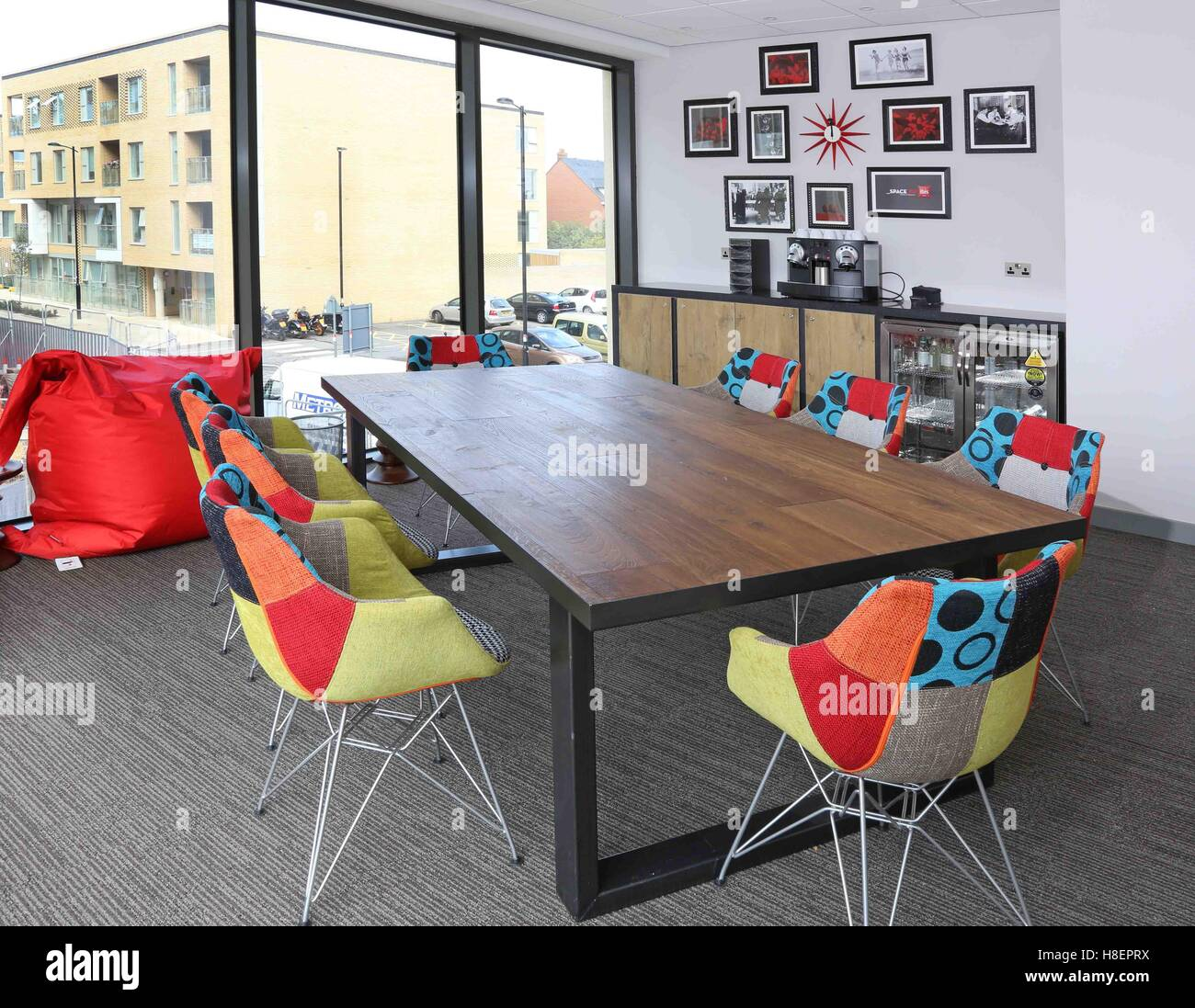 Trendy meeting room in the new Ibis Hotel in Cambridge, UK. Shows multi-coloured fabric chairs, large bean-bag, - Stock Image