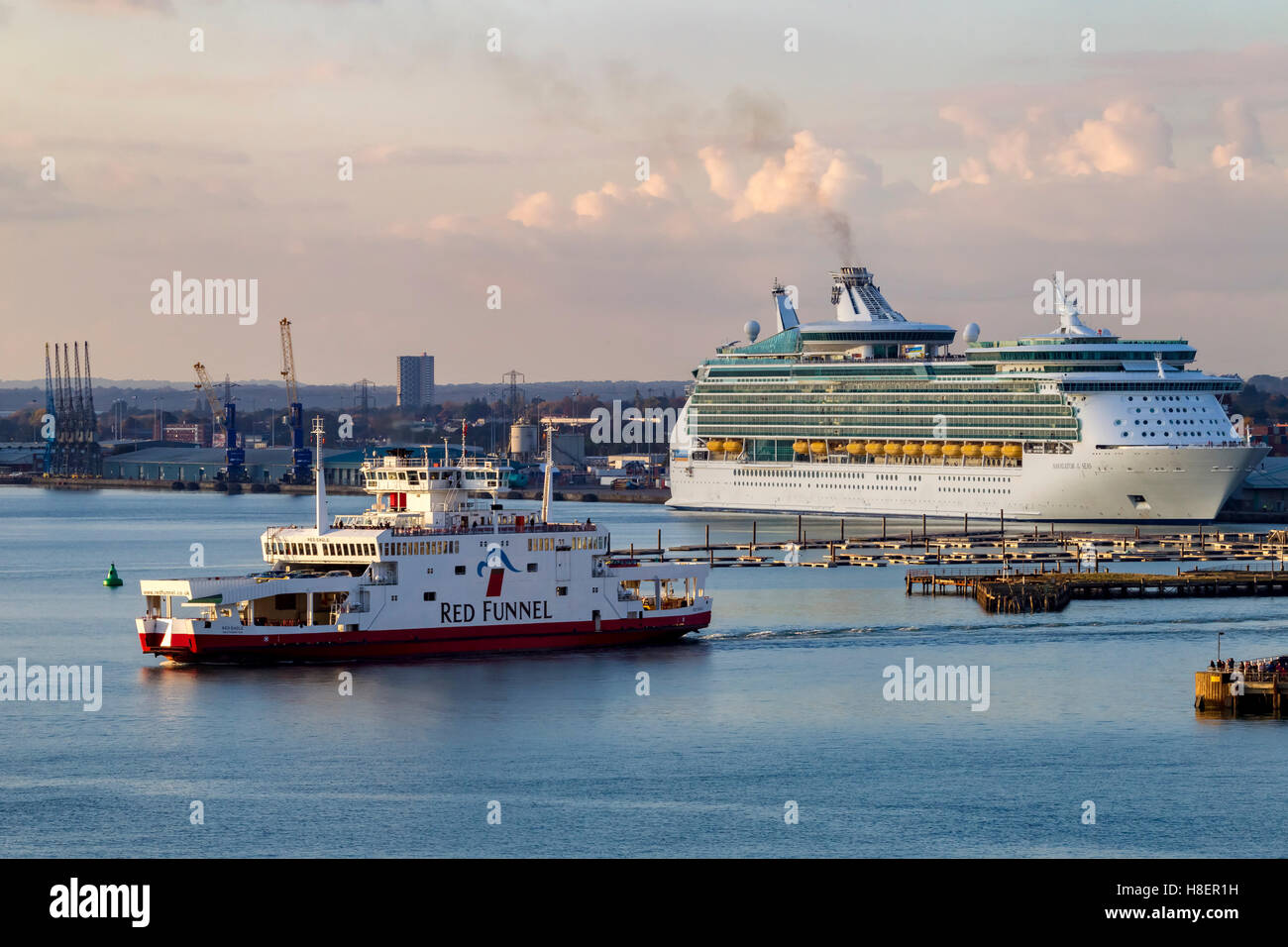 Royal Caribbeans Navigator of the seas moored in Southampton Docks and a Red Funnel ferry leaving port. - Stock Image