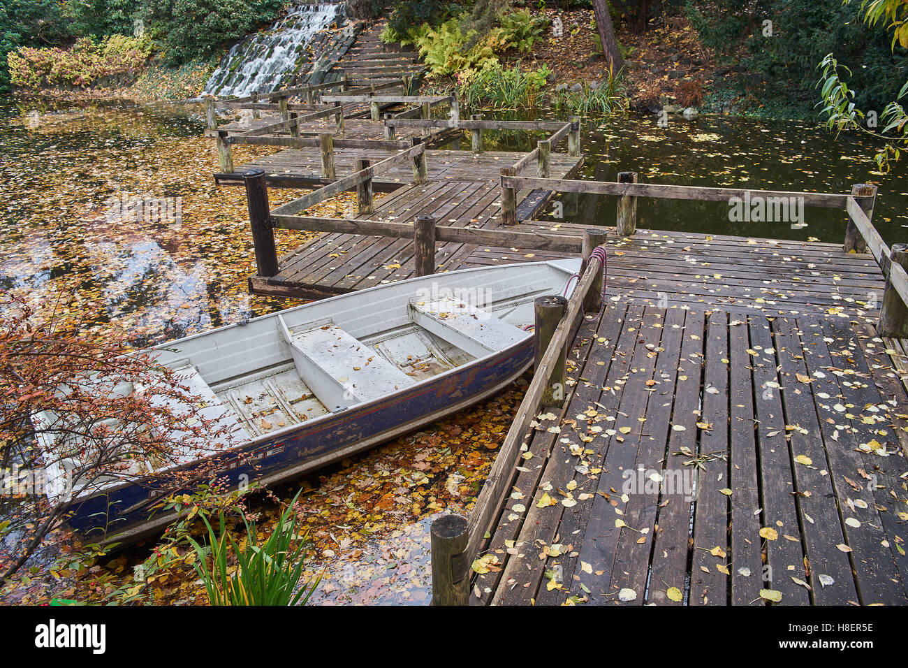 Autumn silence fallen leaves anchored boat quiet water - Stock Image