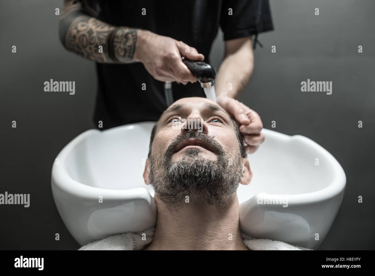 Washing head in barbershop - Stock Image