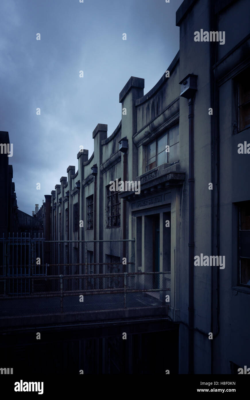 An old industrial building looking dark and foreboding - Stock Image