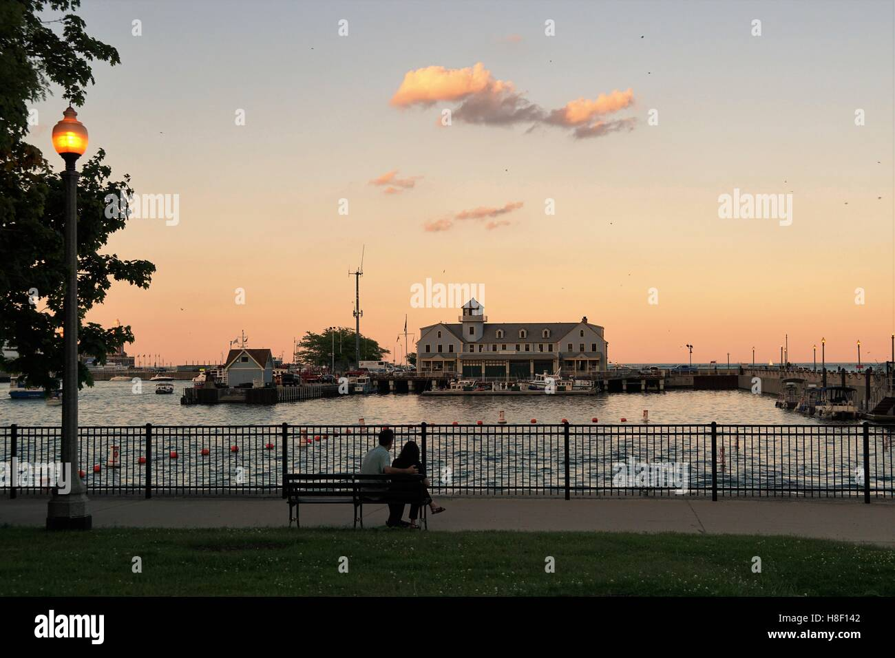 Couple Sitting Watching Sunset Chicago Marine Safety Station / Breakwater Access / Navy Pier / Dusable Harbor - Stock Image