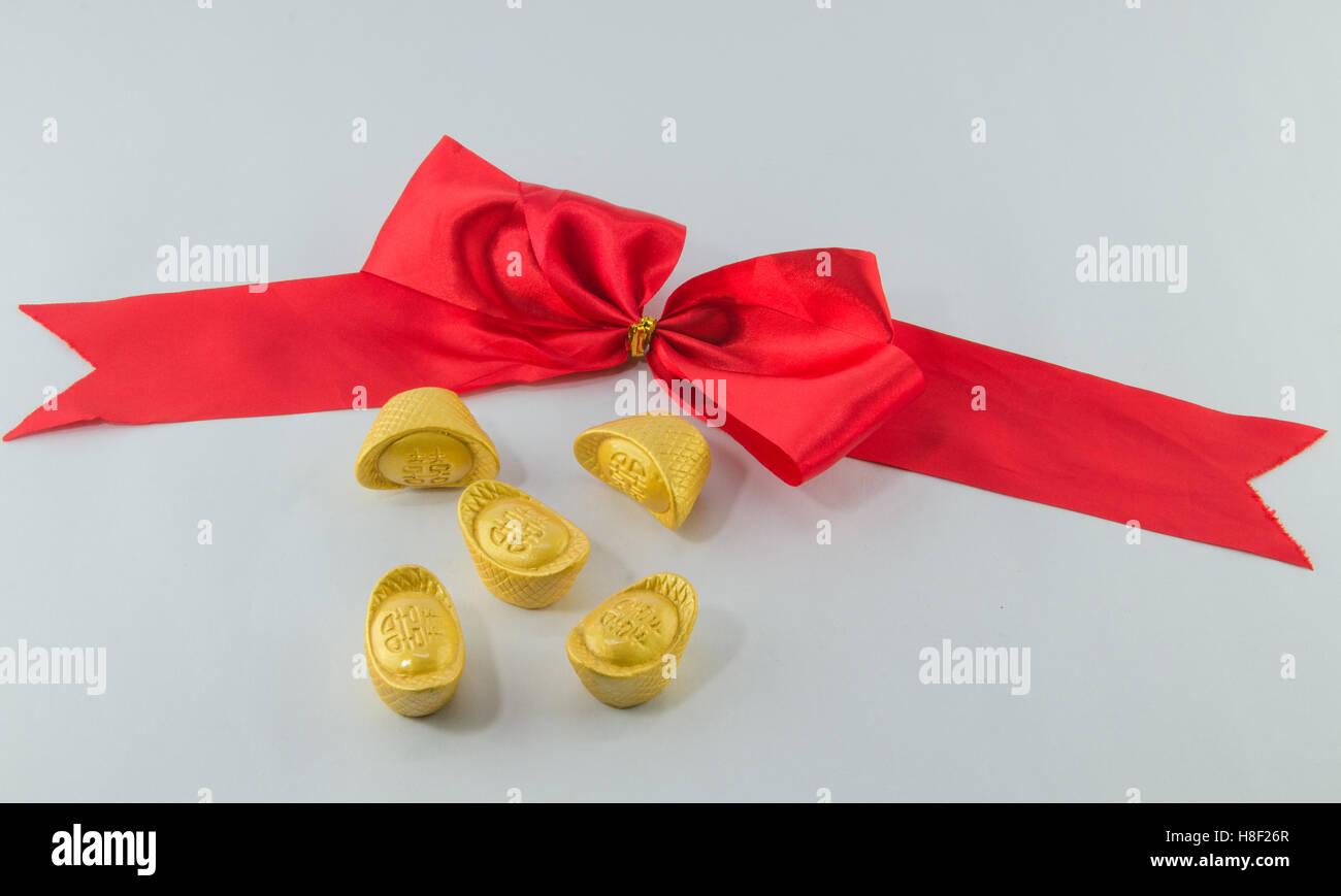 Gold ingot Red ribbon bow on white background. - Stock Image
