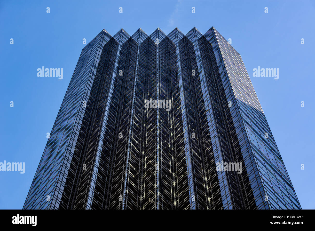 Facade of Trump Tower skyscraper with glass windows and blue sky. Midtown Manhattan, New York City - Stock Image