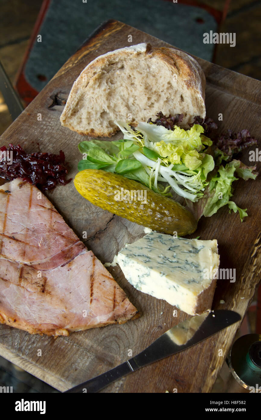 Ploughman's lunch on a wooden platter with cheeese, ham, bread and gherkin. - Stock Image