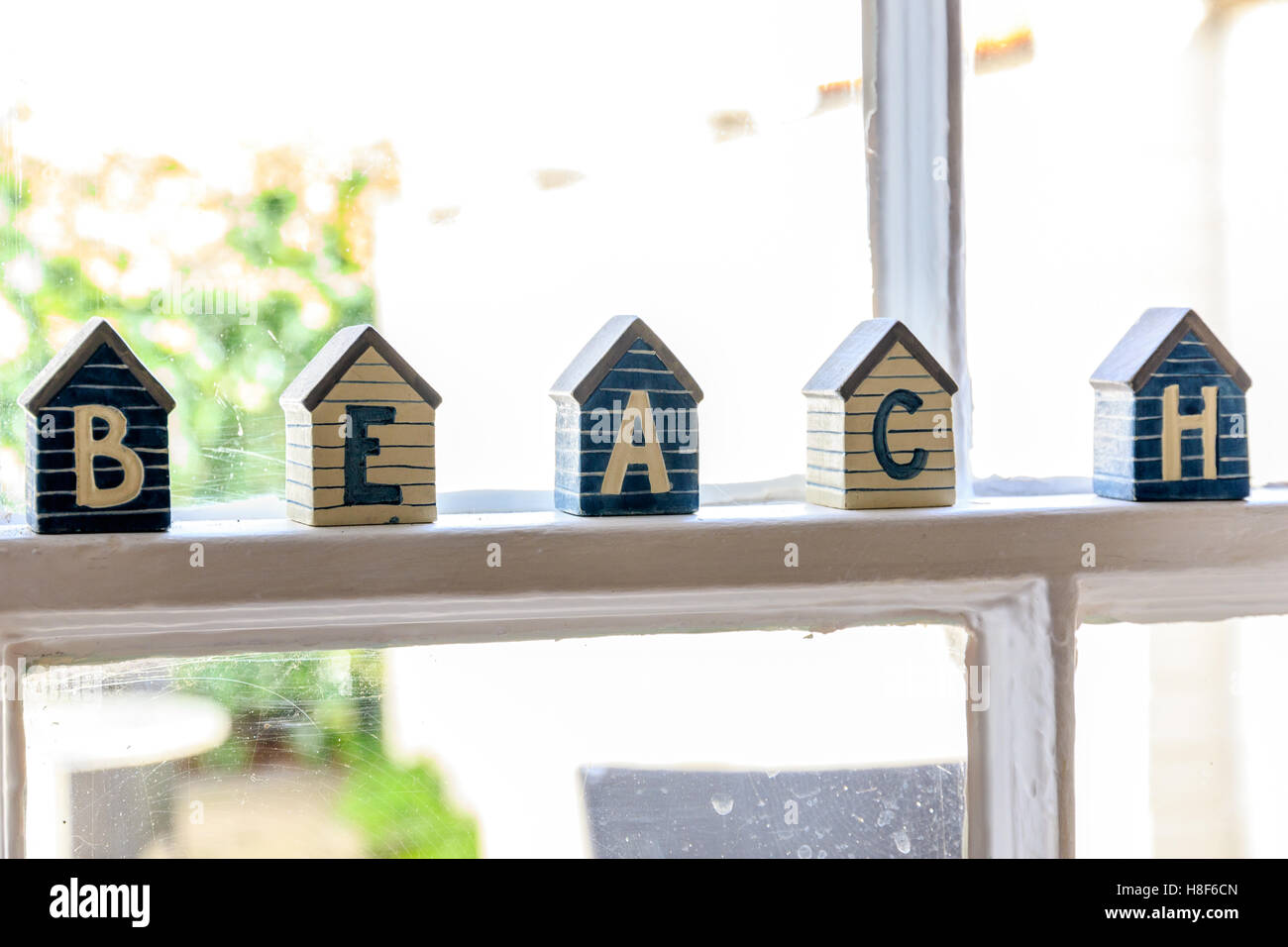 Little beach hut wooden ornaments on window frame composing the word ...