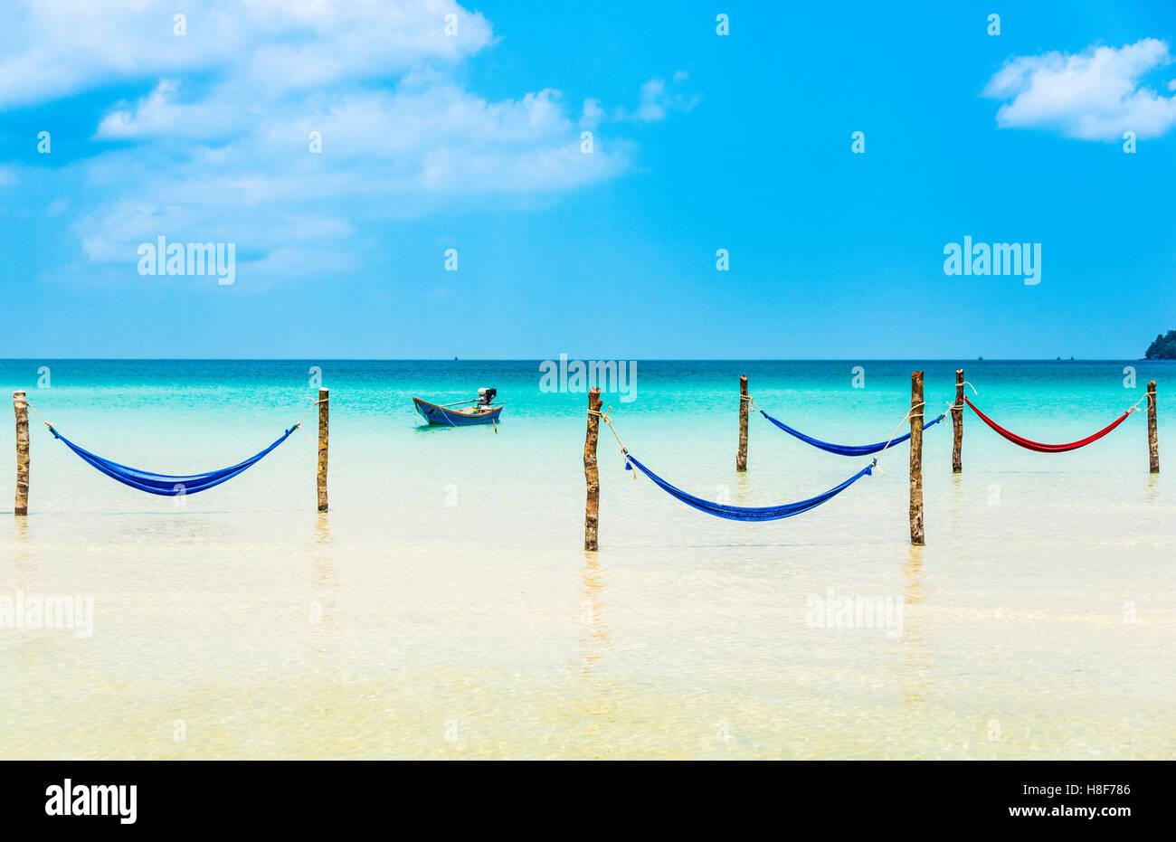 Motorboat, hammocks on idyllic sandy beach, turquoise sea, Saracen Bay, Koh Rong Samloem island, Krong Preah Sihanouk - Stock Image