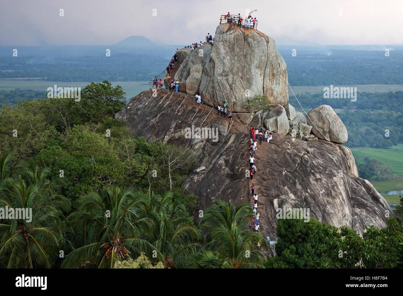 People on Rock of Invitation, Aradhana Gala, Sila Rock, Mihintale, North Central Province, Sri Lanka - Stock Image