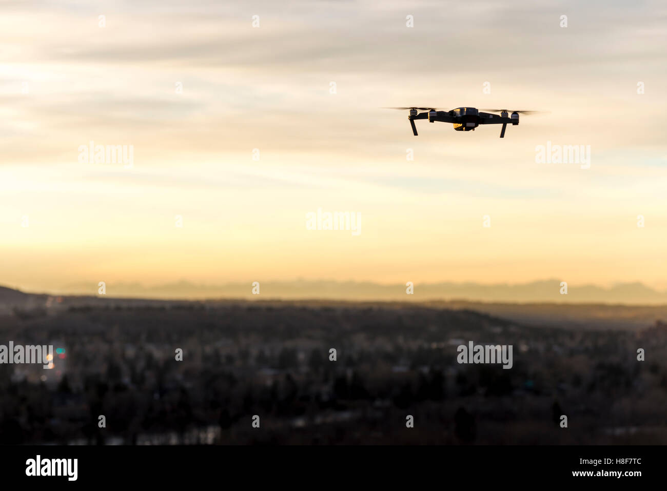 Small modern drone hovering taking picture of sunset - Stock Image