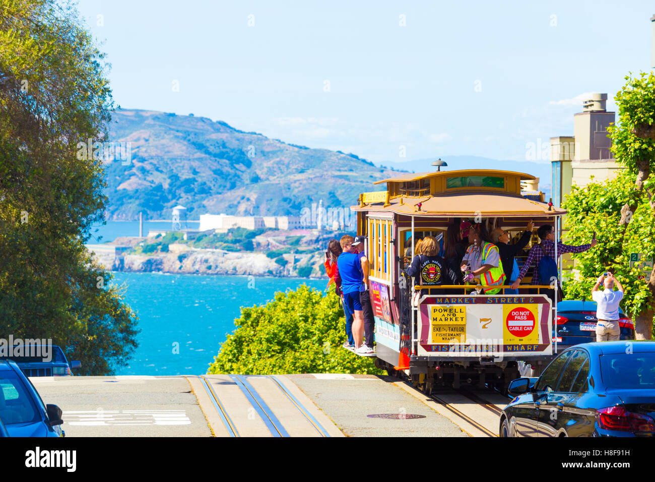 Cable car with tourists riding outside approaching steep precipice edge at peak of Hyde St with amazing view of - Stock Image
