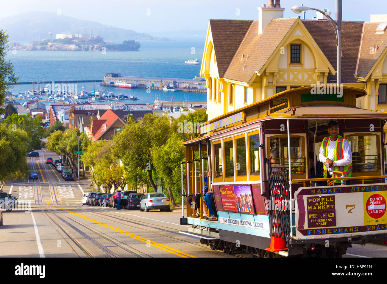Brakeman appying cable car brakes going downhill on steep Hyde Street hill with sweeping view of Alcatraz Prison, - Stock Image