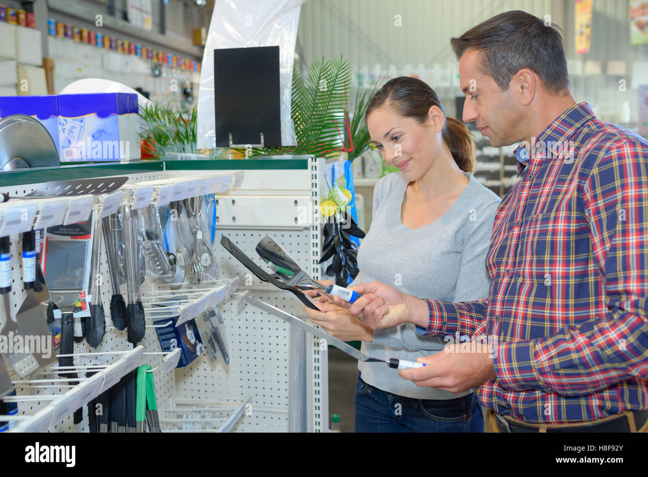Couple looking at tools in hardware shop - Stock Image