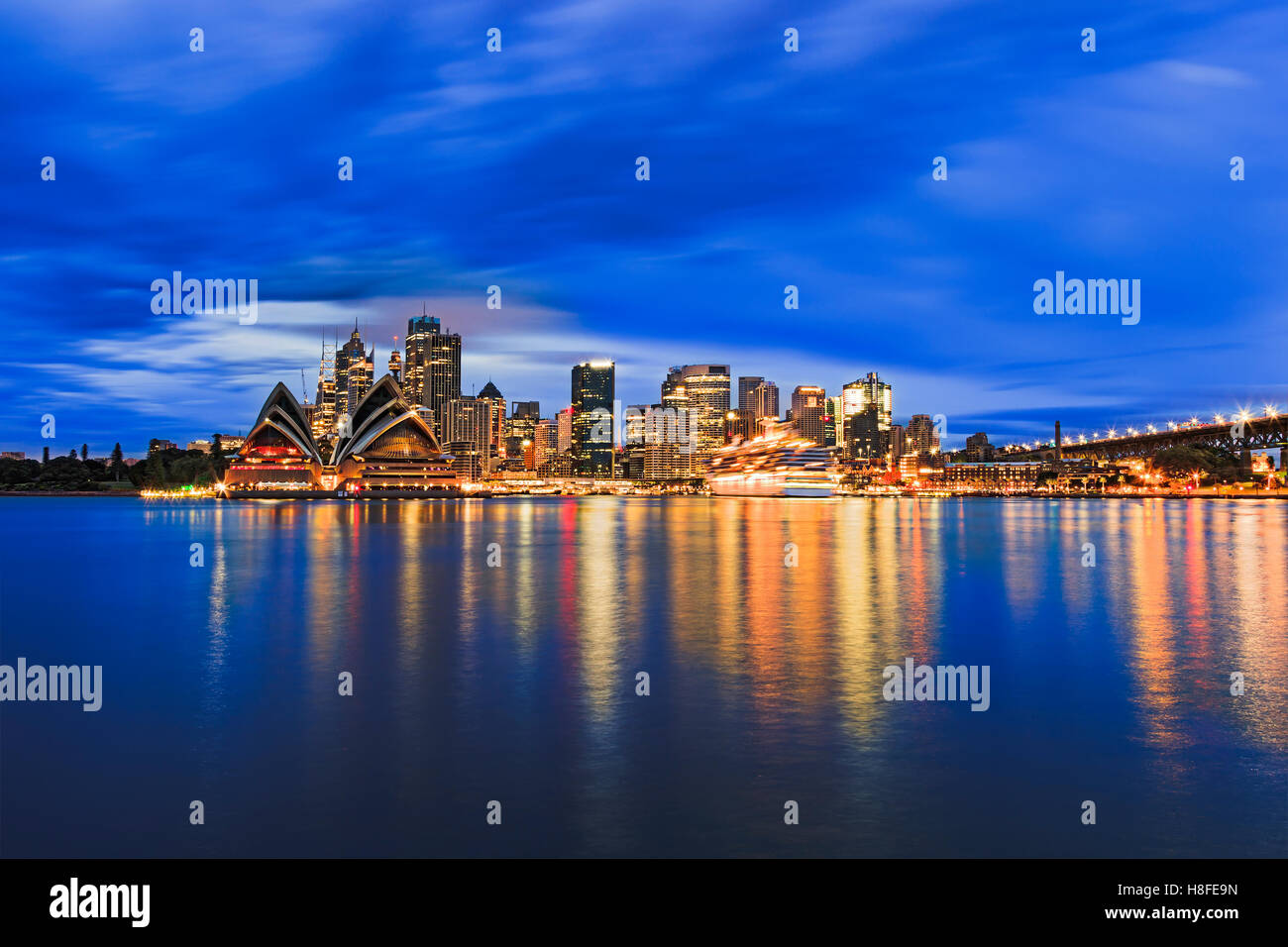 Sydney city CBD across Harbour blurred waters at sunrise when bright downtown lights reflect and blur between blue - Stock Image