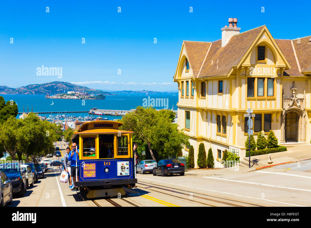 Blue cable car with hanging tourists going uphill on steep Hyde St with sweeping view of Alcatraz Prison, bay water - Stock Image