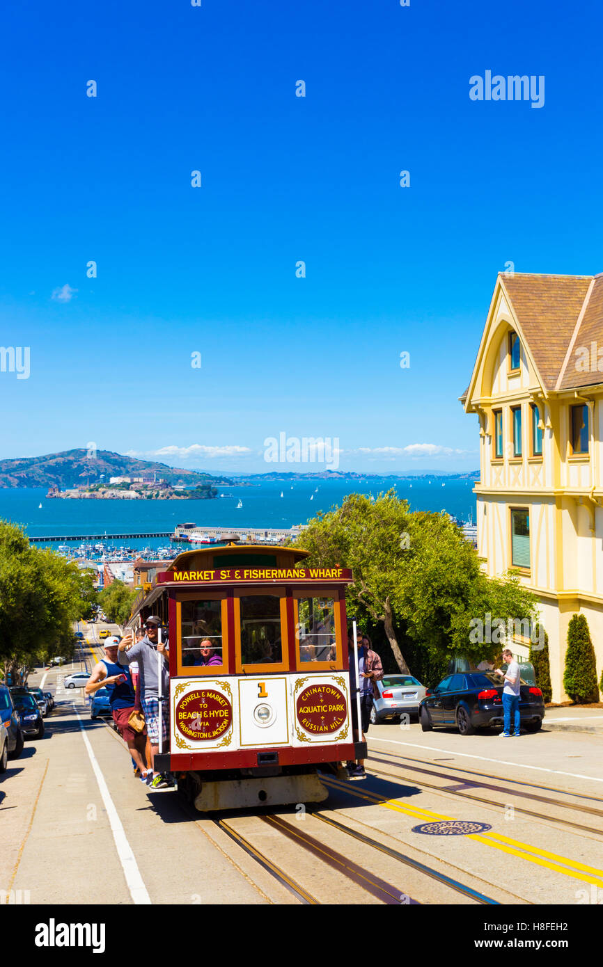 Tourists riding outside cable car climbing steep uphill street on Hyde St with view of Alcatraz Prison and Victorian - Stock Image