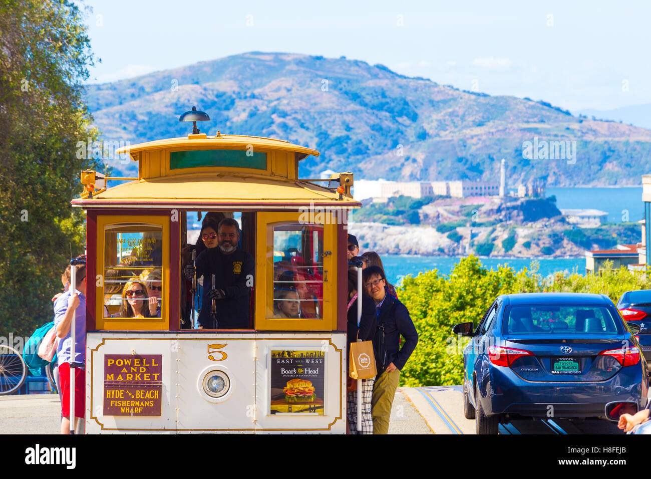 Iconic approaching cable car full of tourists at the top peak of Hyde Street hill overlooking Alcatraz Island with - Stock Image