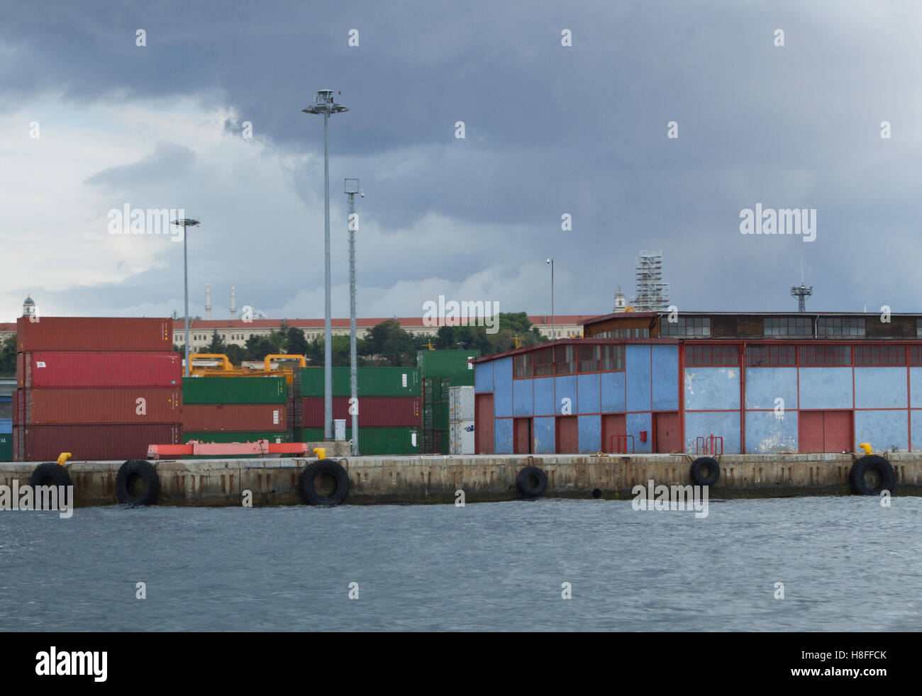 Seaport containers warehouse near sea and storm sky - Stock Image