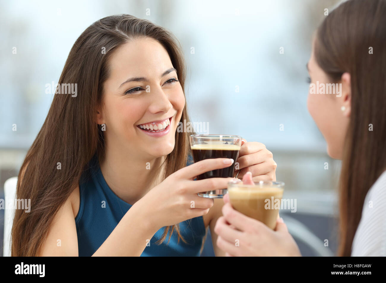Portrait of two women friends talking holding coffee cups in a restaurant - Stock Image