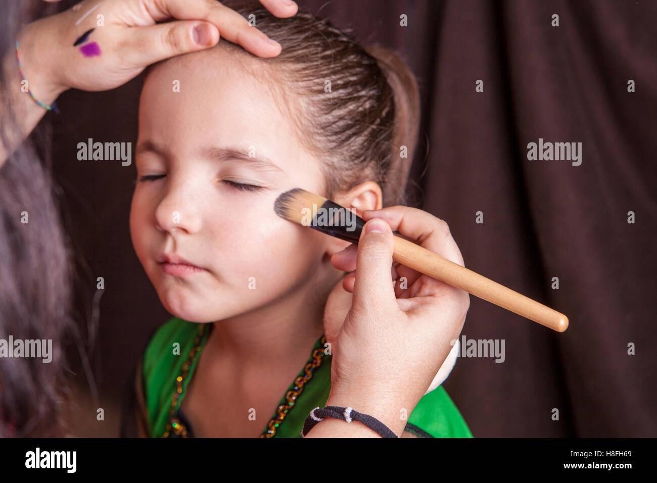 Little cute girl making facepaint before halloween party. The make-up artist is applying some foundation - Stock Image