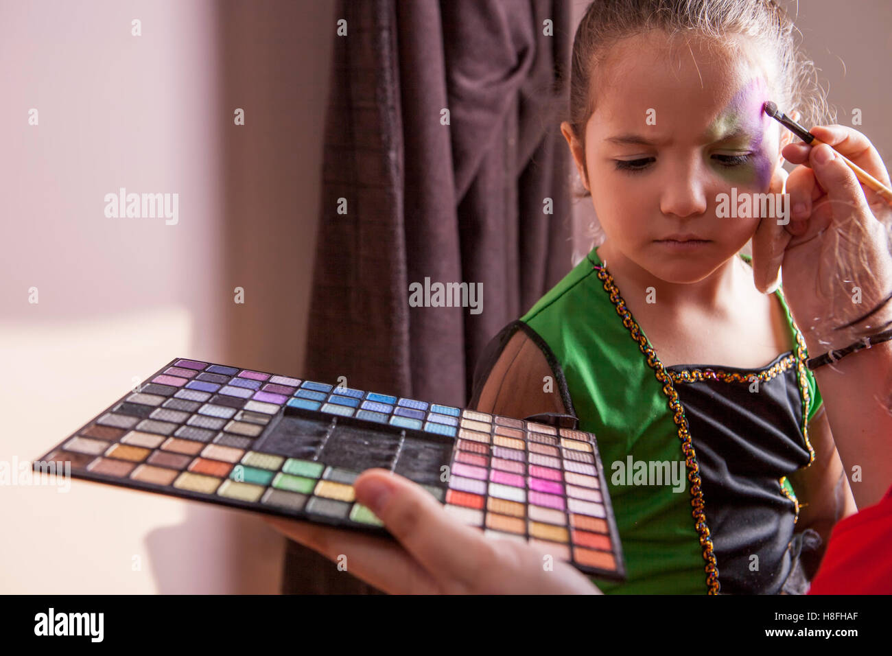 Little cute girl making facepaint before halloween party. The make-up artist is applying some colors - Stock Image