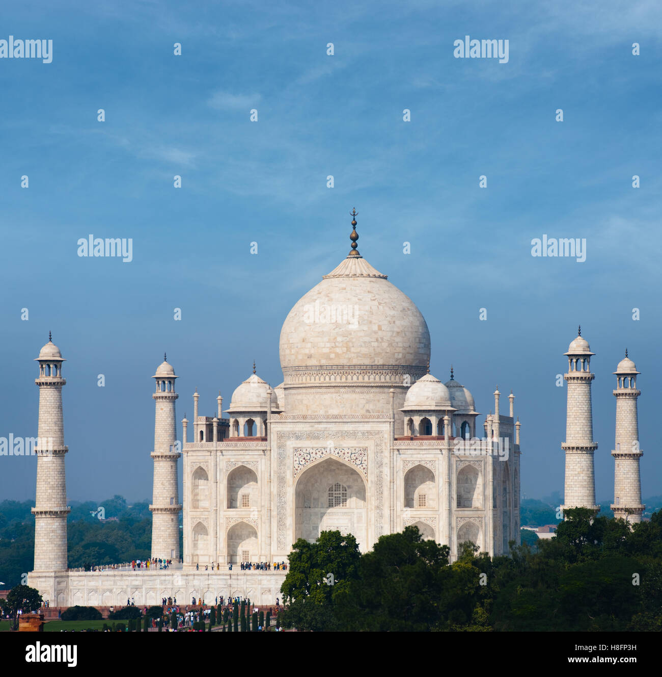 Distant telephoto view of sun shining brightly on white marble of the Taj Mahal from outside the grounds at daytime - Stock Image
