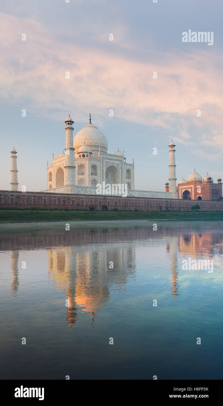 Majestic Taj Mahal marble glowing orange and red mosque beautifully reflected in the gentle Jamuna river on morning - Stock Image