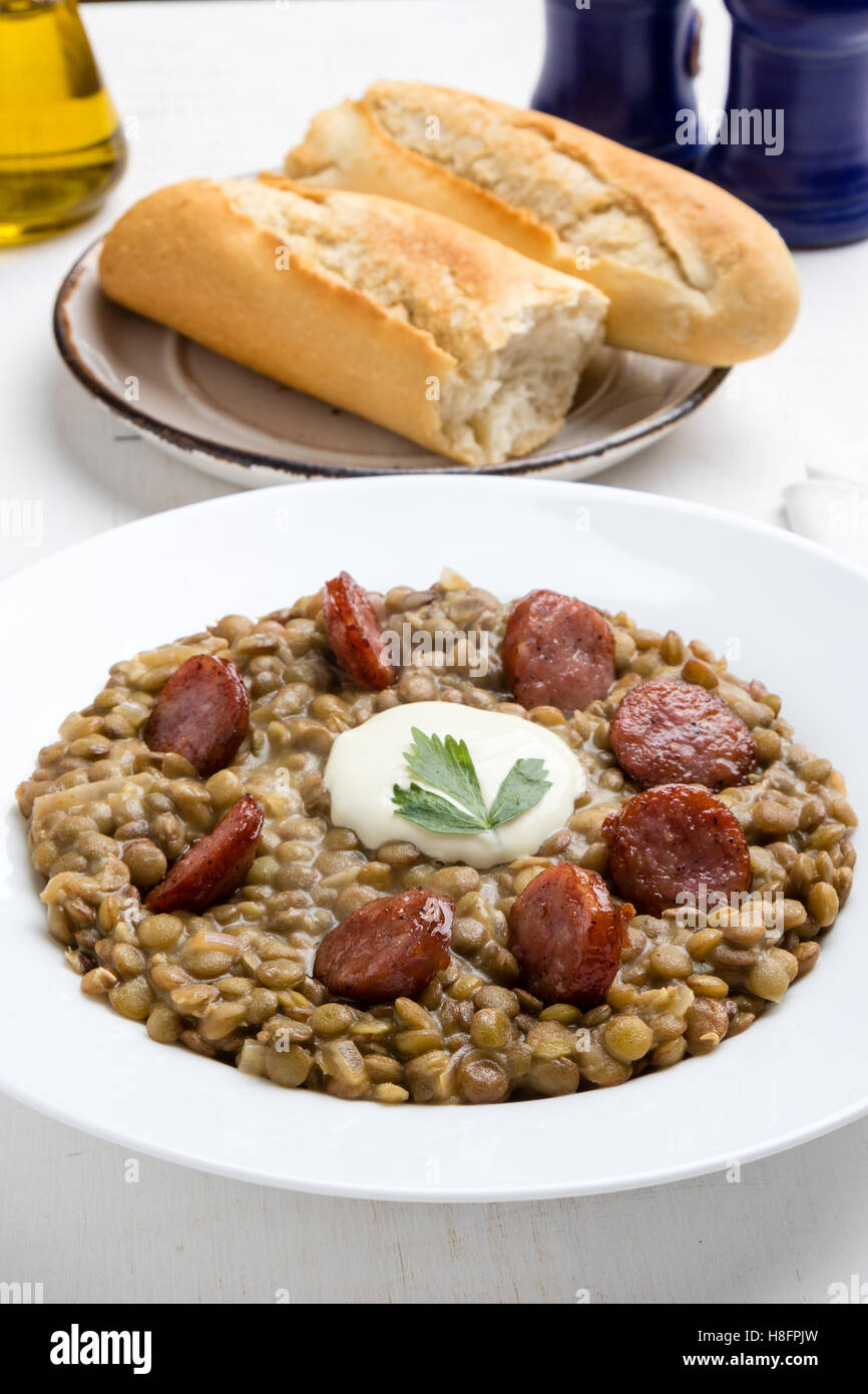green lentil stew with sausage in white plate Stock Photo