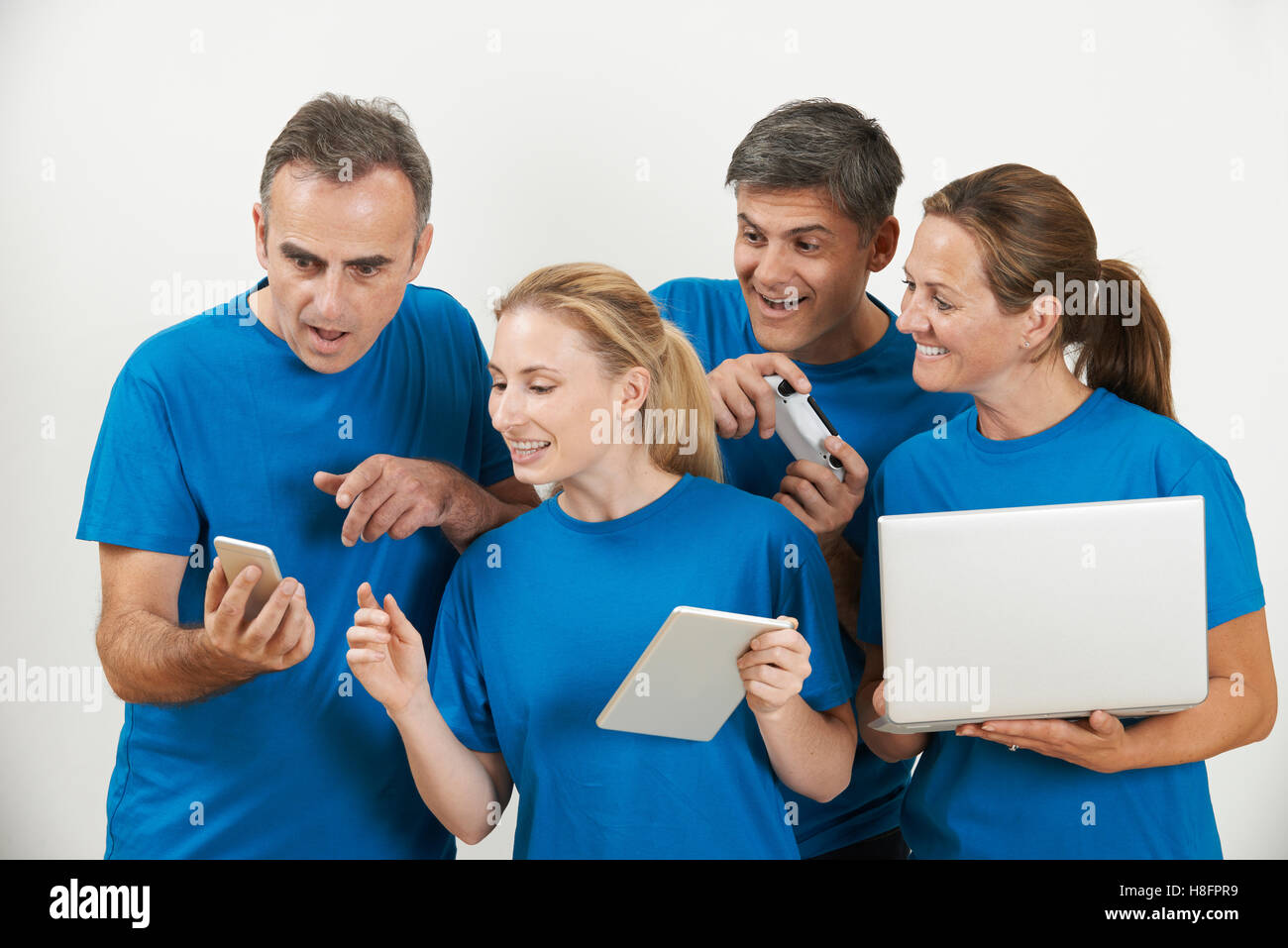 Sales Team Wearing Uniform With Selection Of Techno Gadgets - Stock Image