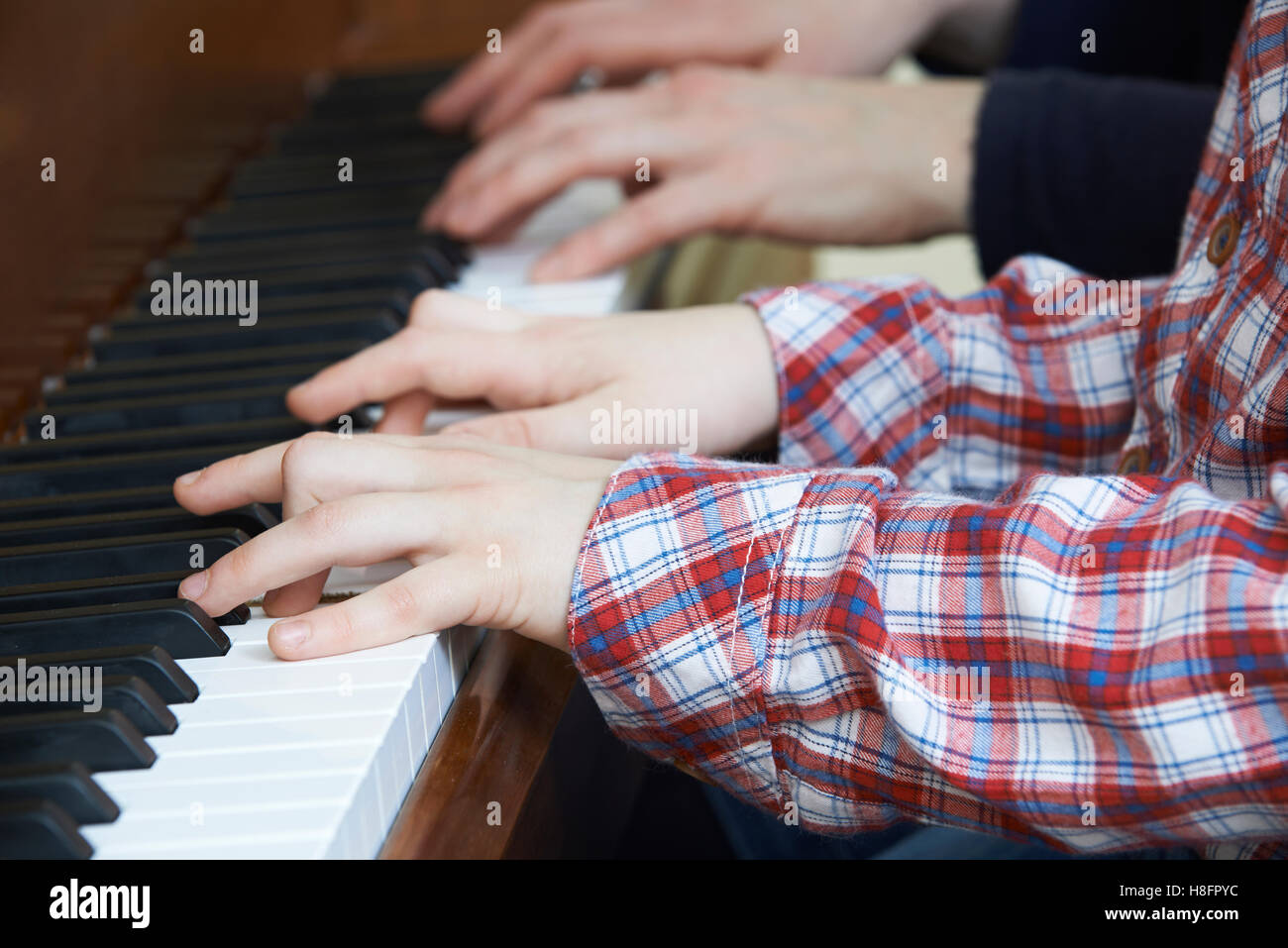 Close Up Of Boy Playing Piano Duet With Teacher - Stock Image