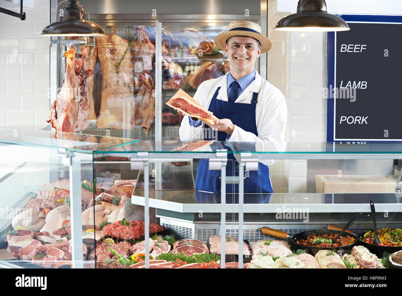 Portrait Of Butcher Standing Behind Counter - Stock Image
