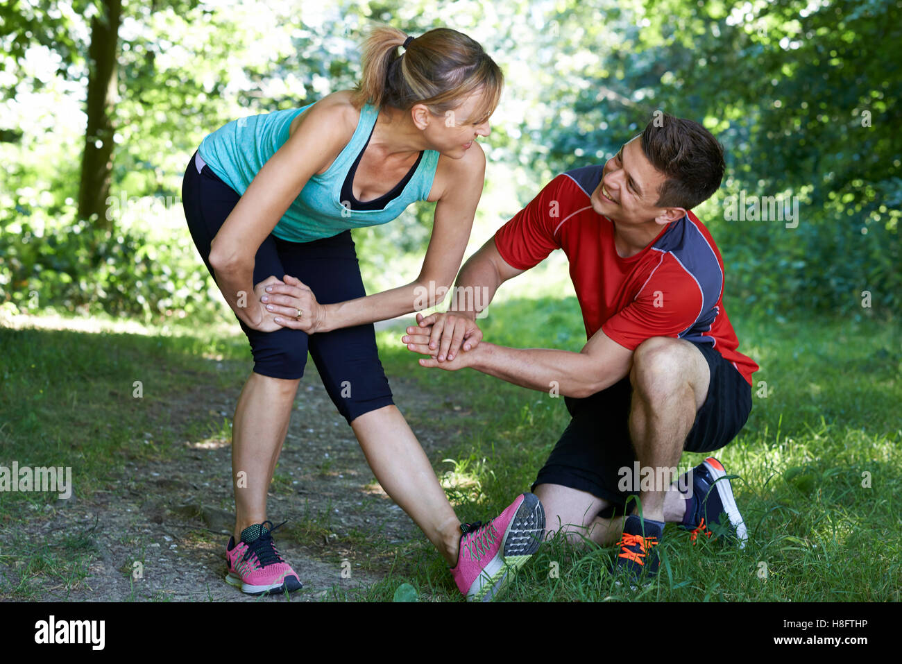 Mature Woman Exercising With Personal Trainer In Park - Stock Image