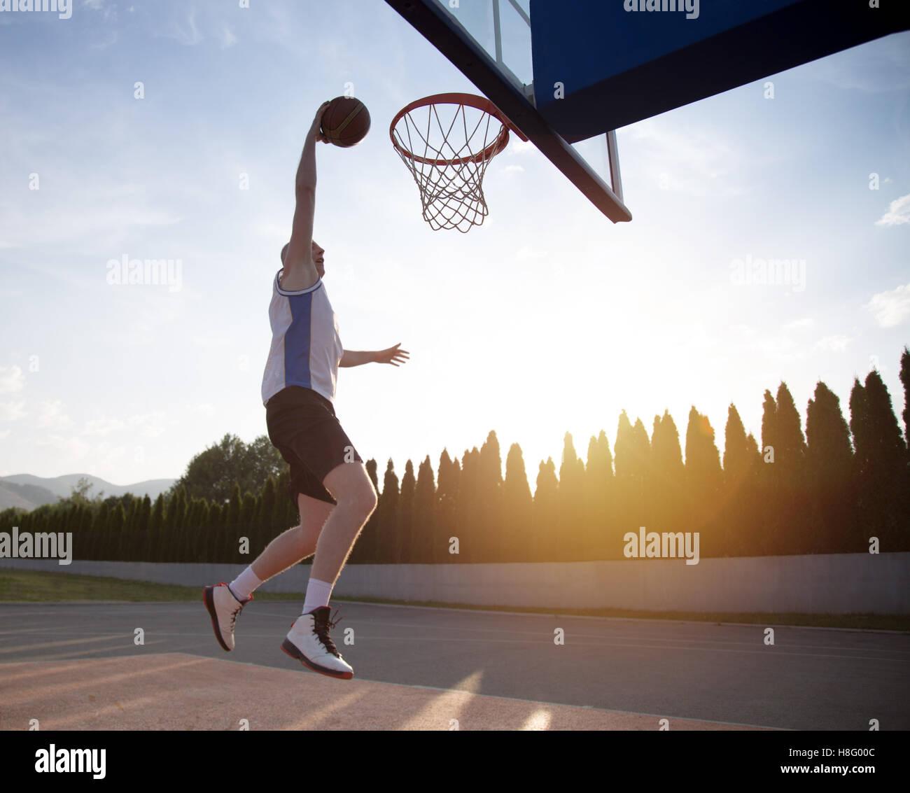 Young man jumping and making a fantastic slam dunk playing stree - Stock Image