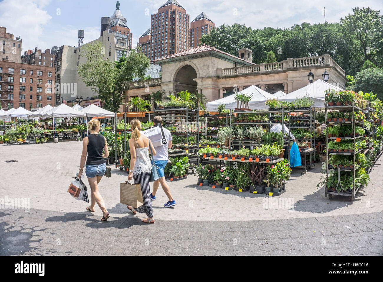 3 twenty somethings are diverted by gardening area of Union Square greenmarket providing plants for city terraces - Stock Image