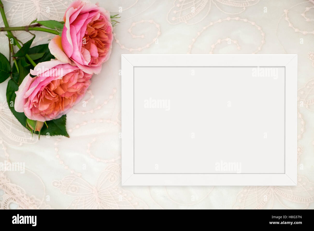White flat lay landscape frame mockup on lace, roses beside the frame, overlay your quote, promotion, headline, Stock Photo