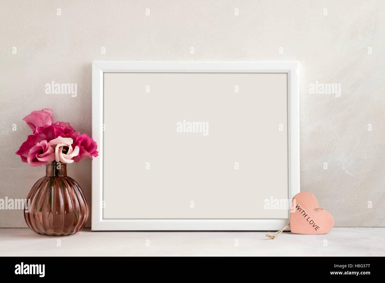 White landscape frame mockup, vase of flowers & pink heart beside the frame, overlay quote, promotion, headline, Stock Photo