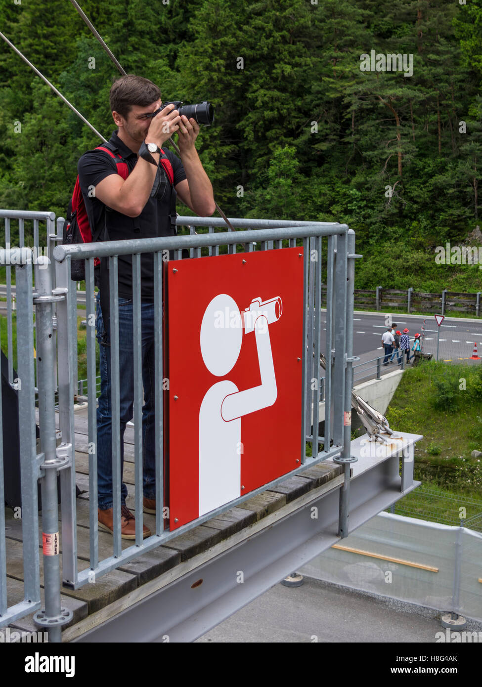 Young caucasian male taking a picture with his camera from a viewpoint designated with a large viewpoint sign. Canton - Stock Image