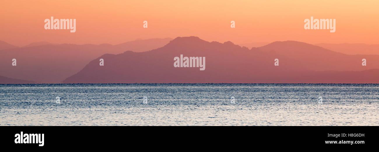 Mainland Greece at sunrise from Poros, Kefalonia. - Stock Image