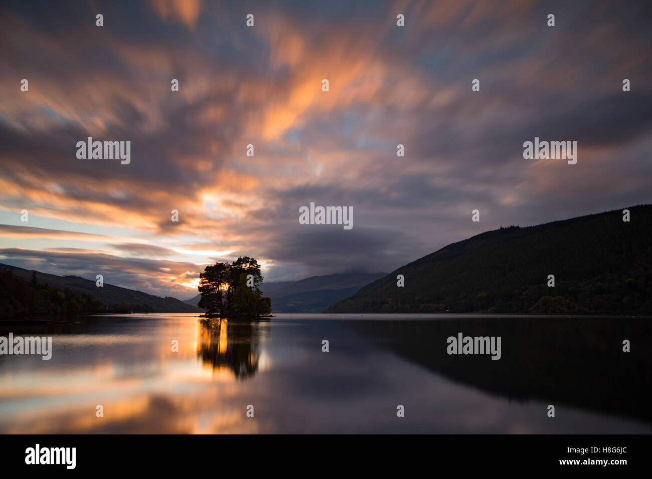 Loch Tay, Perthshire, Scotland, reflects the light from the setting sun as it passes behind the trees on one of - Stock Image