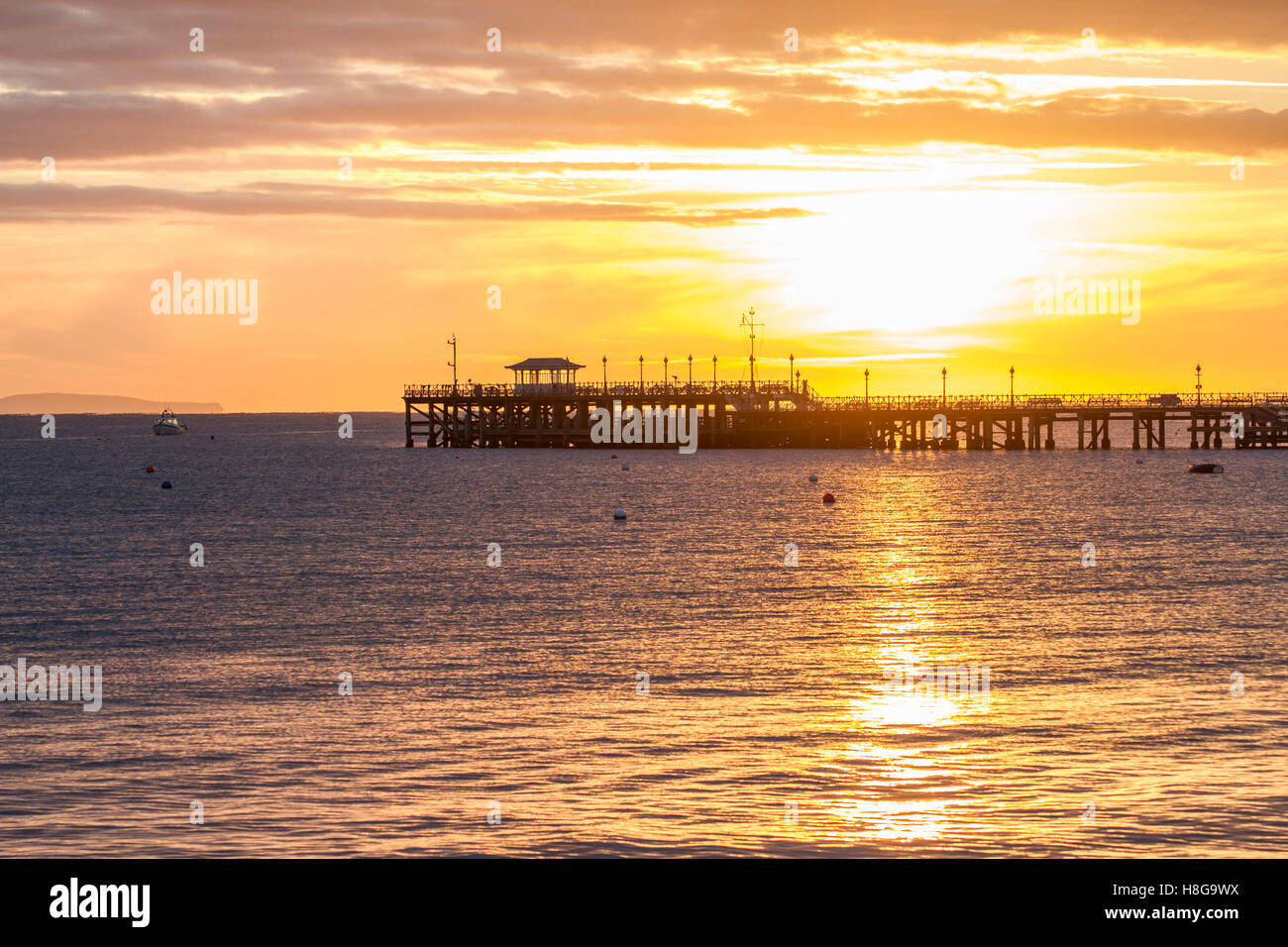 Beautiful Sun Rising Over Silhouette Pier In Swanage Bay Stock Photo
