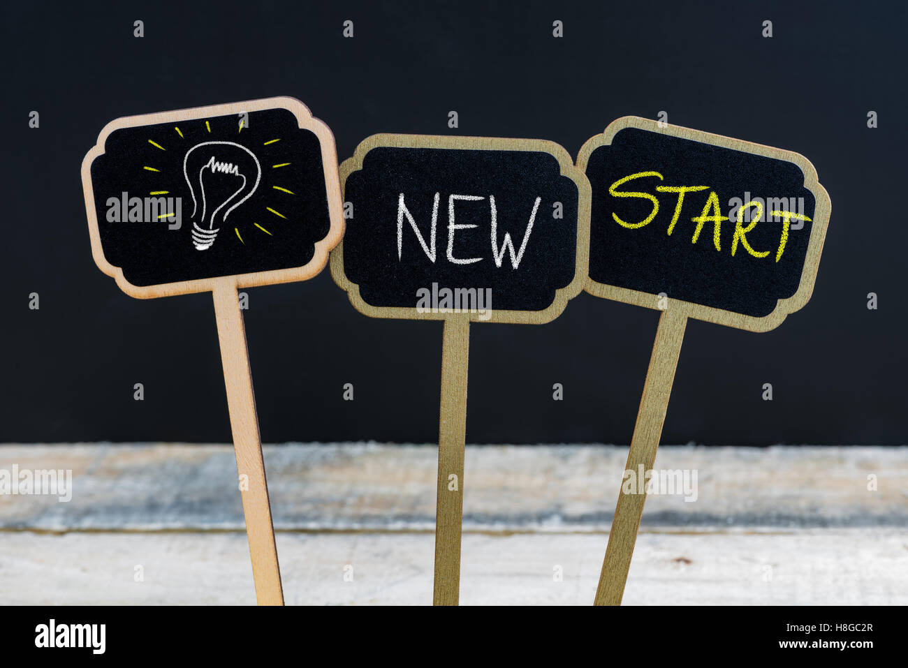 Concept message NEW START and light bulb as symbol for idea written with chalk on wooden mini blackboard labels - Stock Image