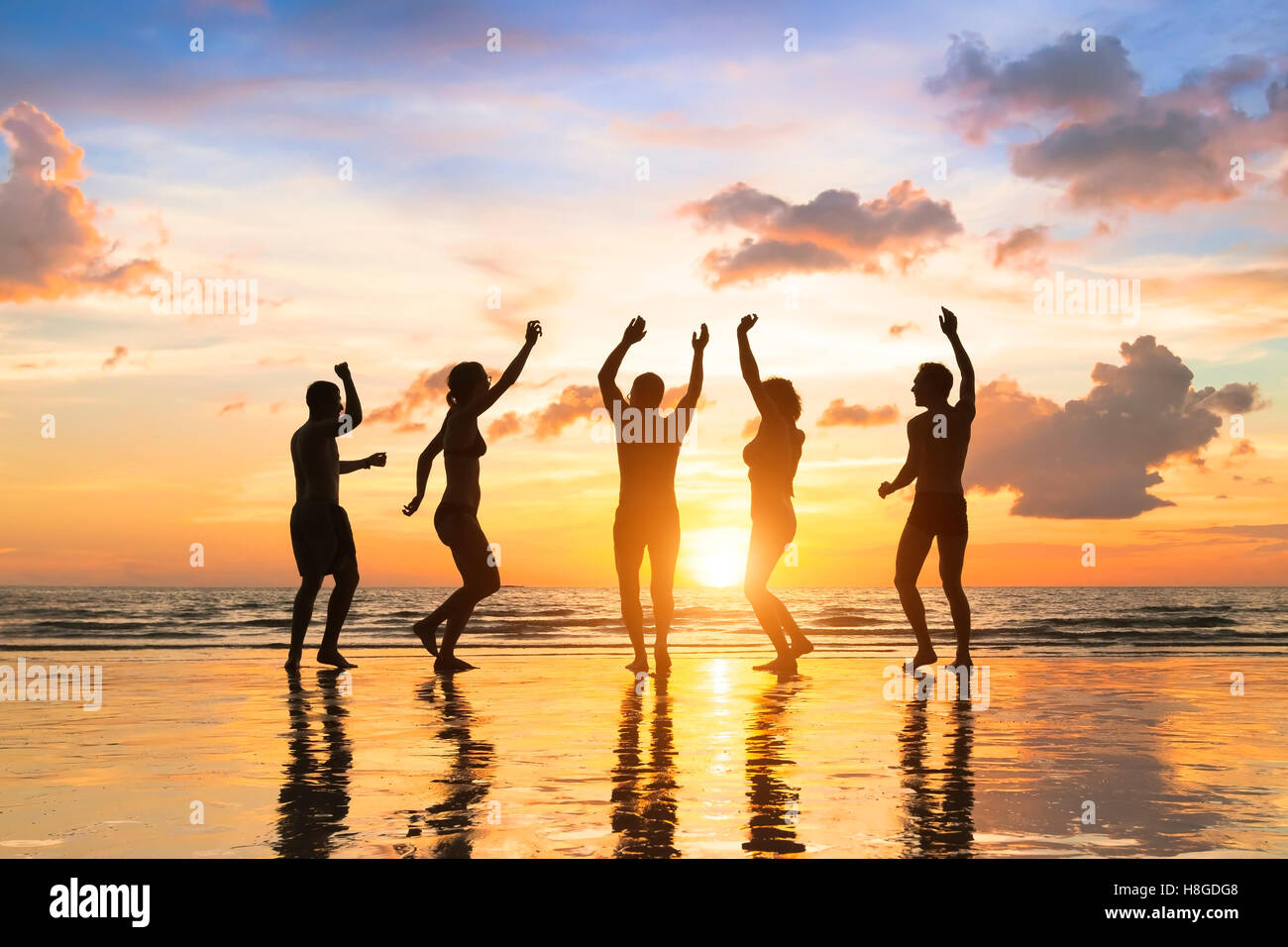 Group of happy people having fun dancing at a beach party, summer vacation, full moon, Thailand - Stock Image