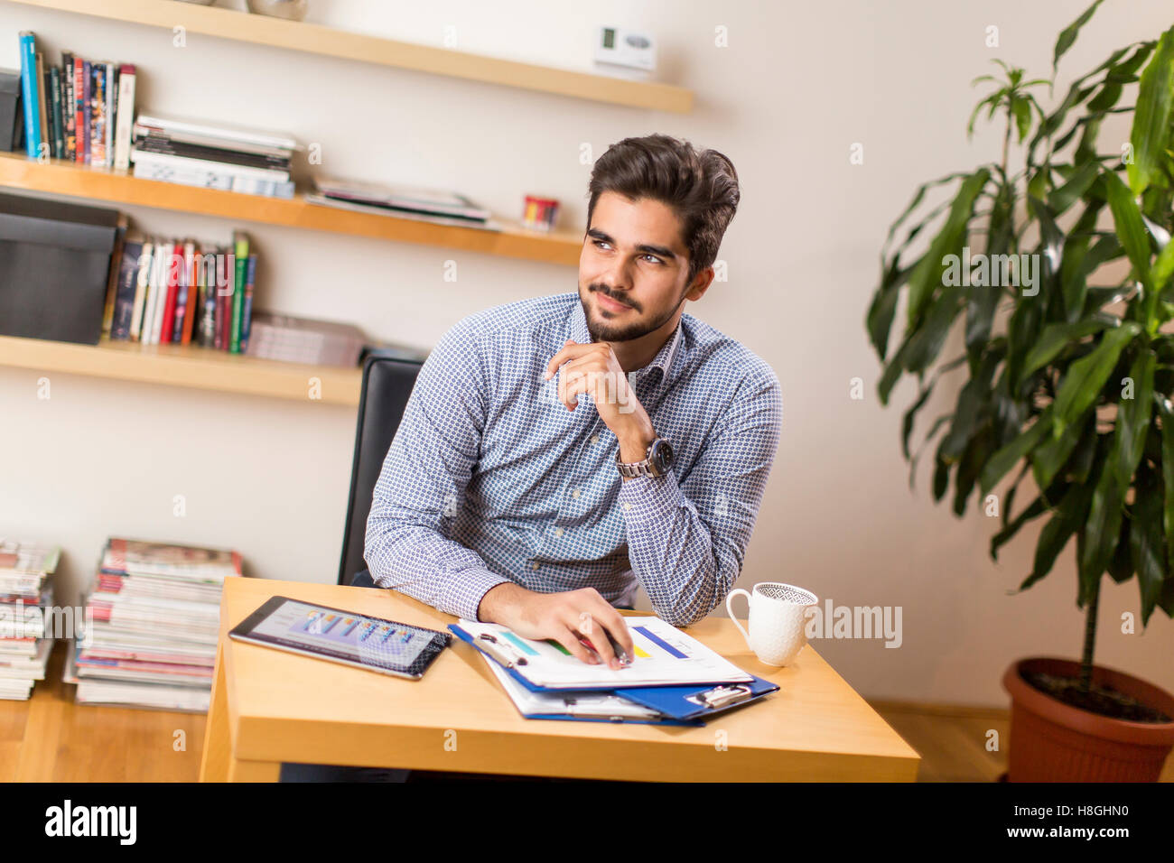 Young freelancer analyzes statistical report at the desk - Stock Image