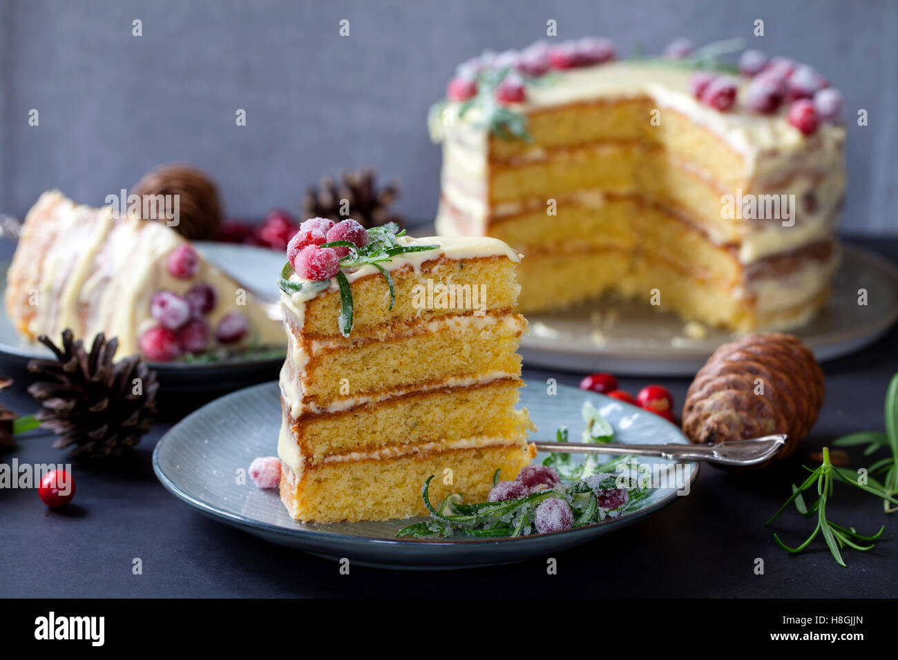 layered Christmas cake with sugared cranberries and rosemary - Stock Image