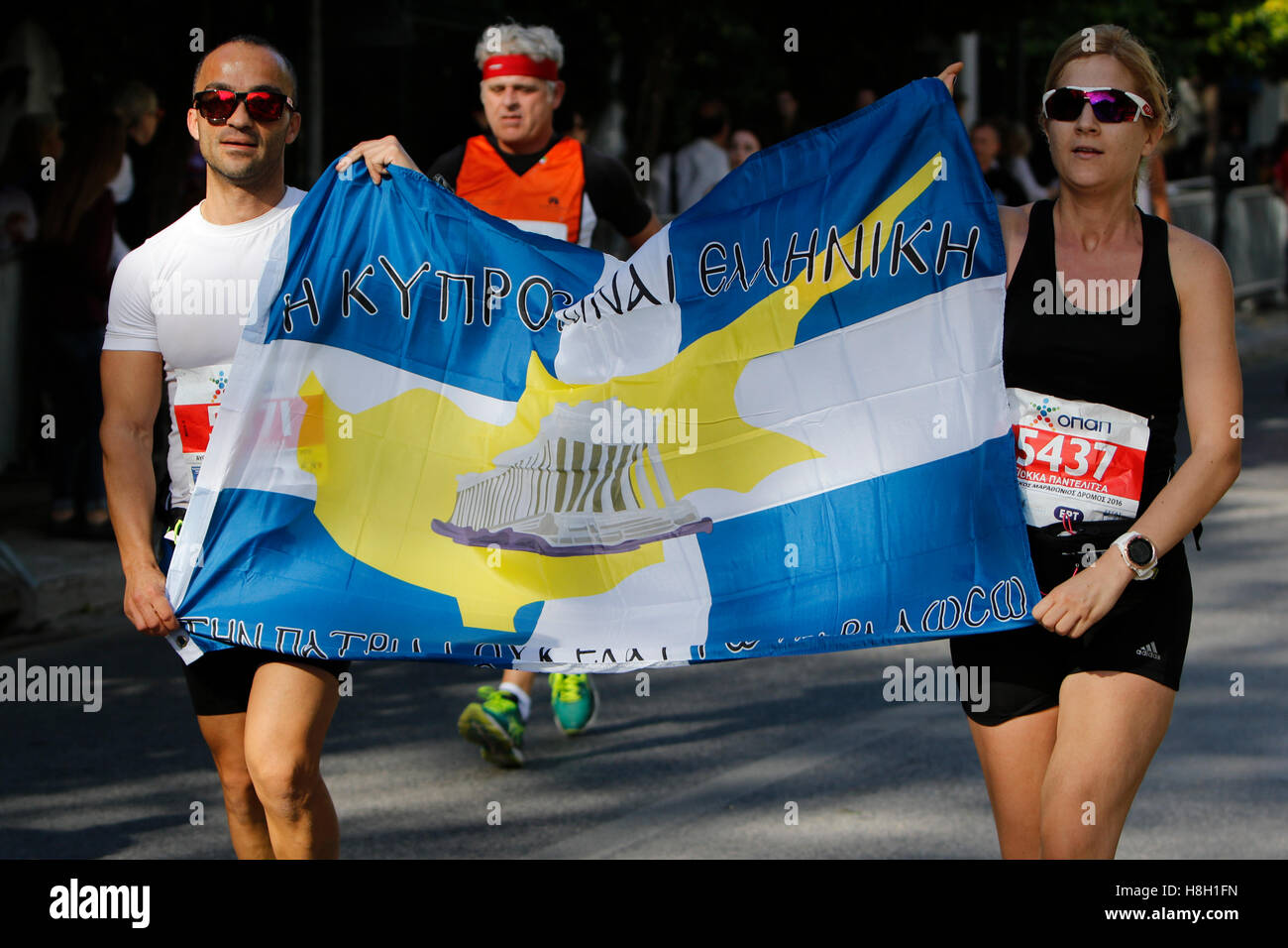 Athens, Greece. 13th November 2016. Two runners carry a Greek Cypriot flag between them. Thousands of people from Stock Photo