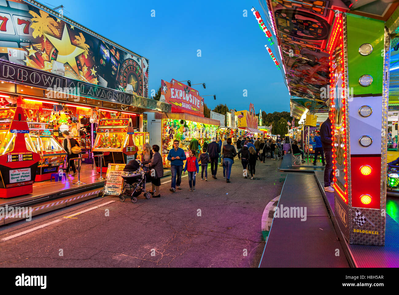 People walking by illuminated stalls and attraction at Luna Park in Alba, Italy. - Stock Image